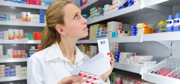 pharmacist looking over shelve of medical supplies